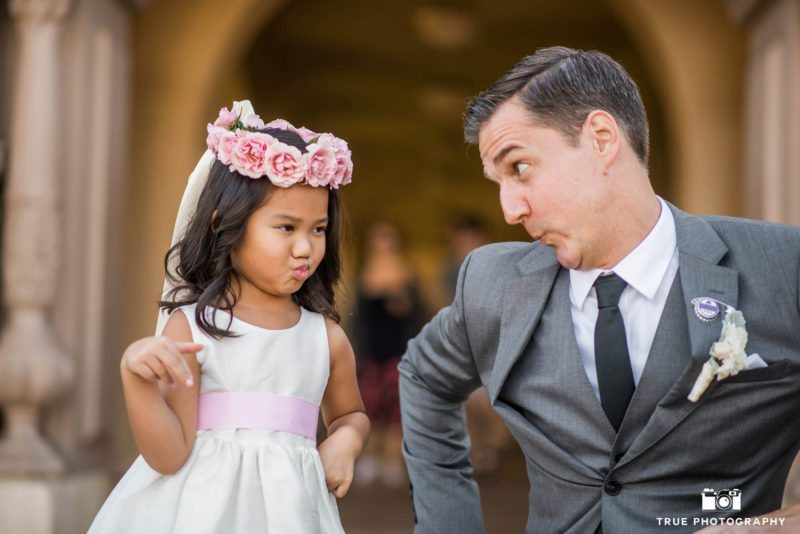 Cute photo of Groom and Flowergirl making silly faces