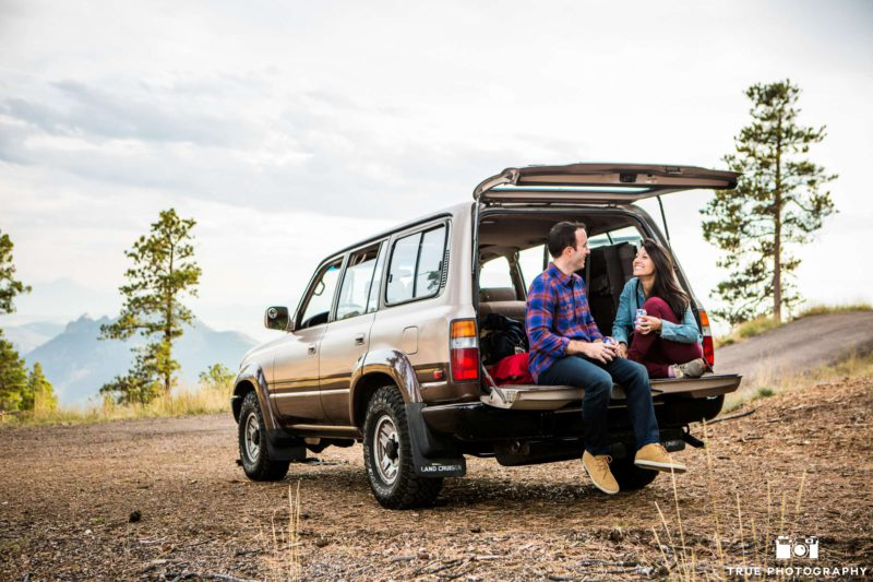 Engaged couple tailgate on campgrounds.