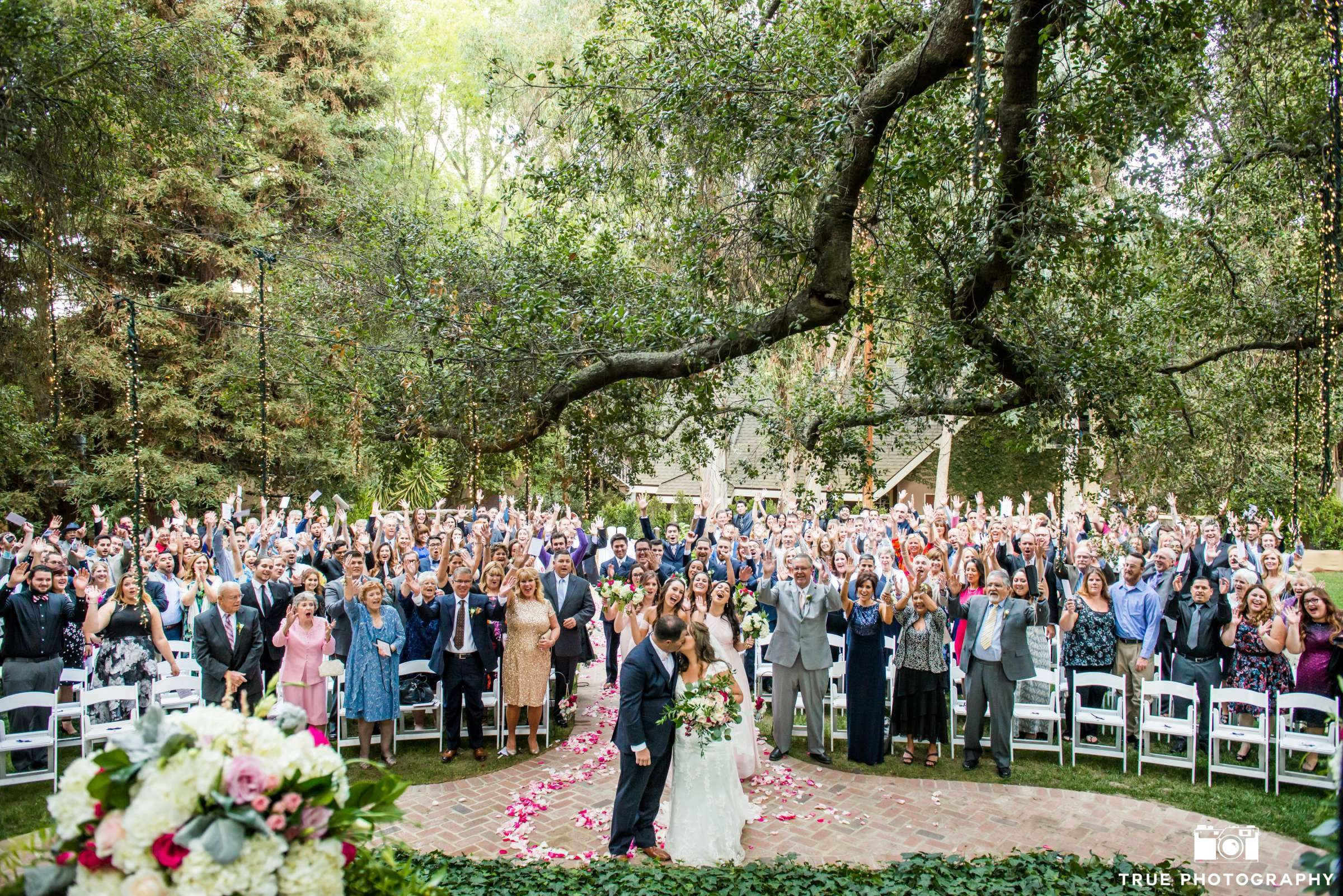 a couple takes a photo with everyone at their ceremony at once.