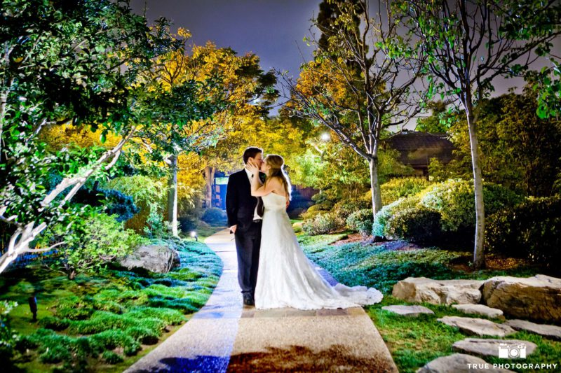 Bride and groom stand in Japanese Garden