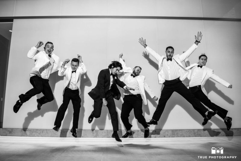 Black and white photo of groomsmen jumping in air