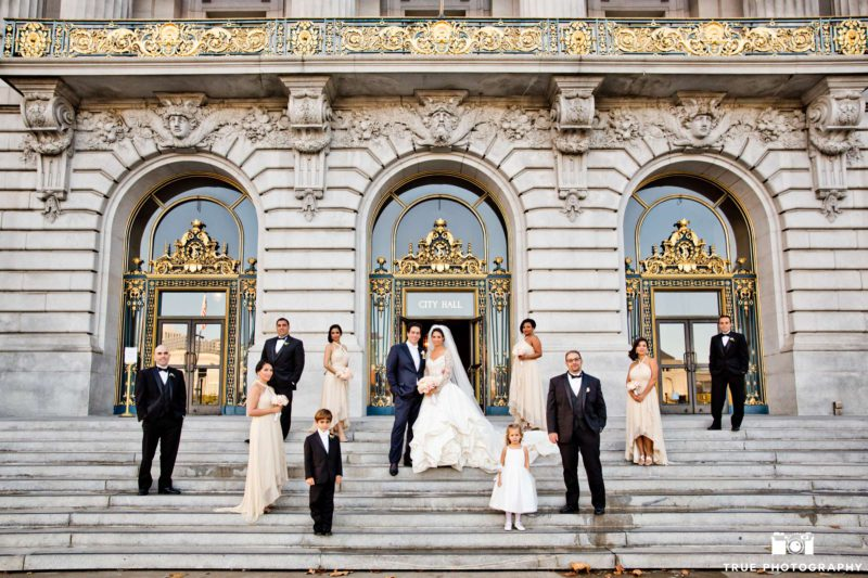 A bridal party scatters out for a stylized portrait on a staircase.