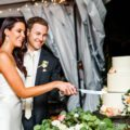 Bride and Groom cut rustic wedding cake during reception