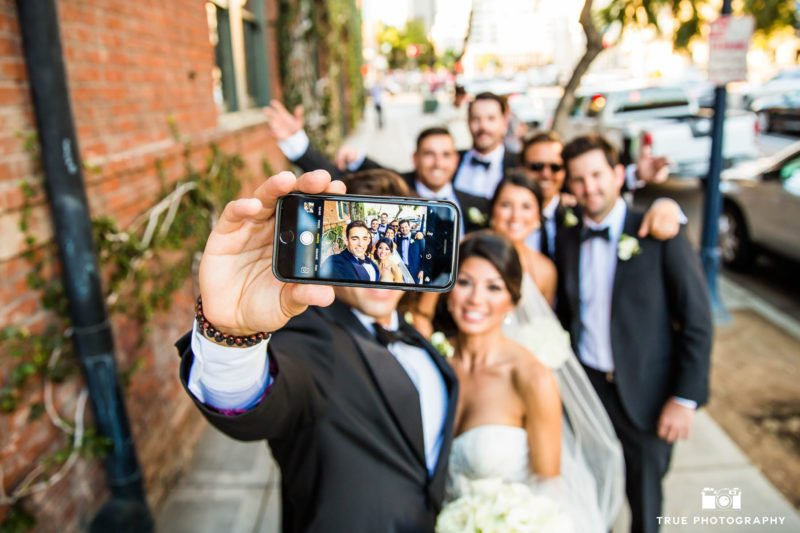 Bridal party take selfie with bride and groom in downtown