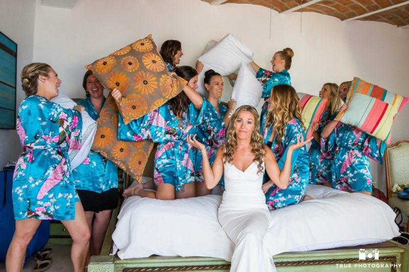 Bride makes funny face while bridesmaids pillow fight
