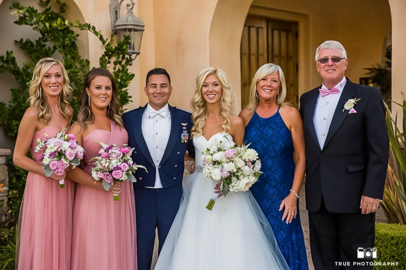 Parents and siblings of the bride pose with the groom.