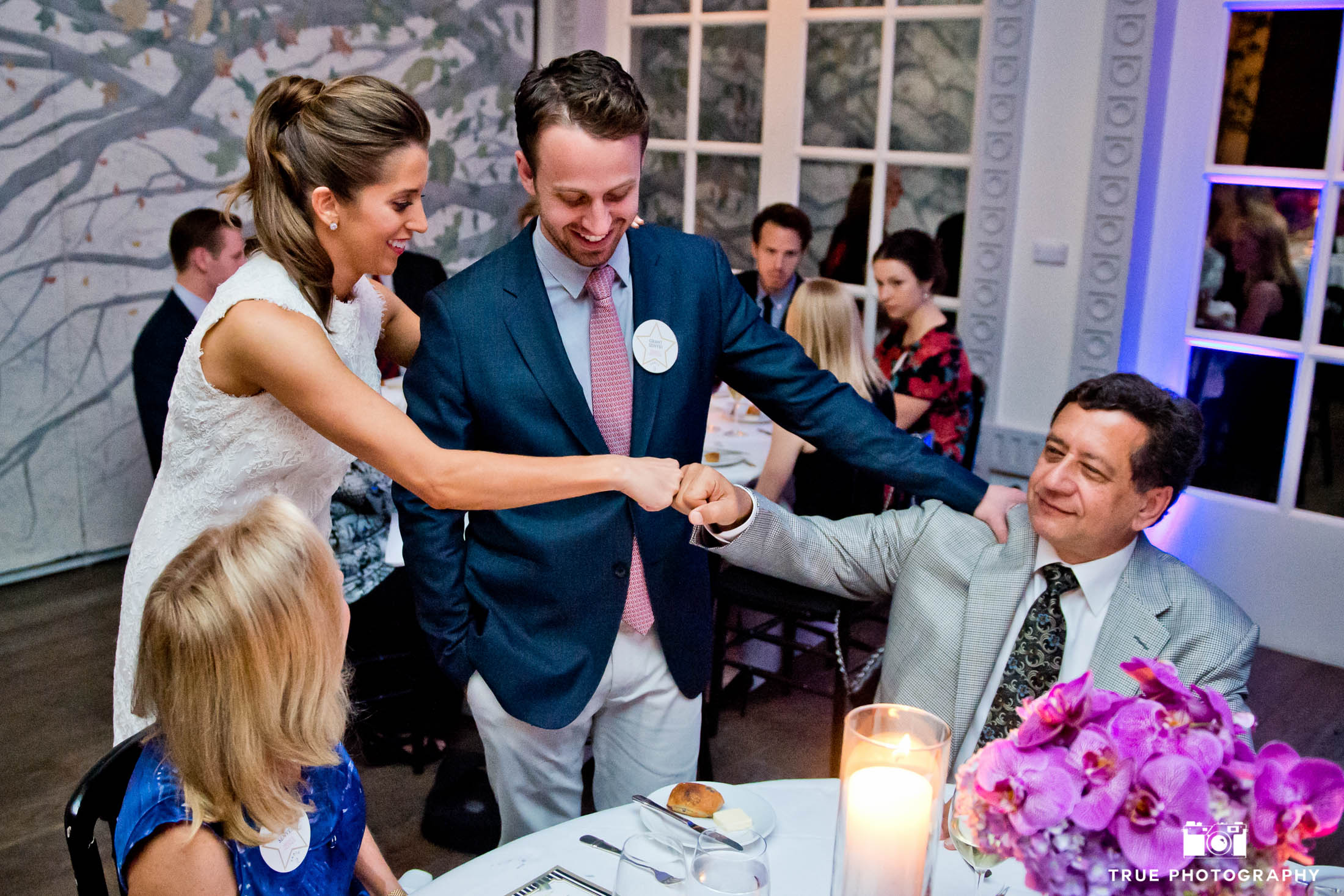 Bride and guest pound fists during reception.
