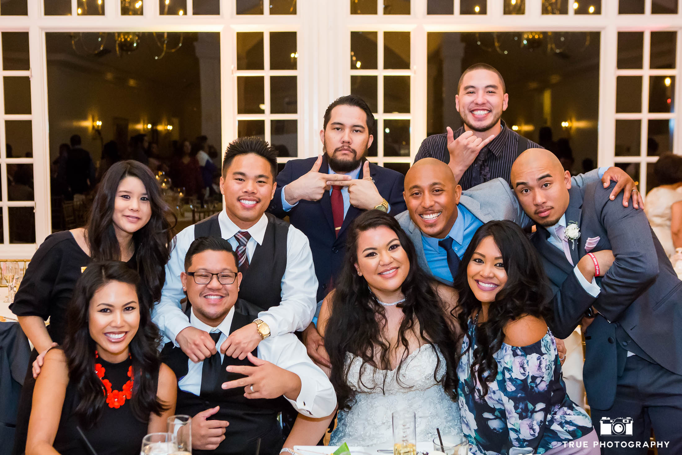 A Bride and groom have their guest join them at their table for a fun photo.