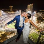 Night photo of bride and groom overlooking Petco Park and kissing
