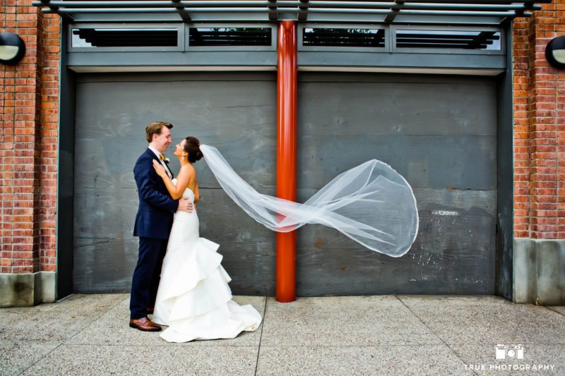 Bride and groom embracing in front of grey wall with veil blowing in wind on wedding day
