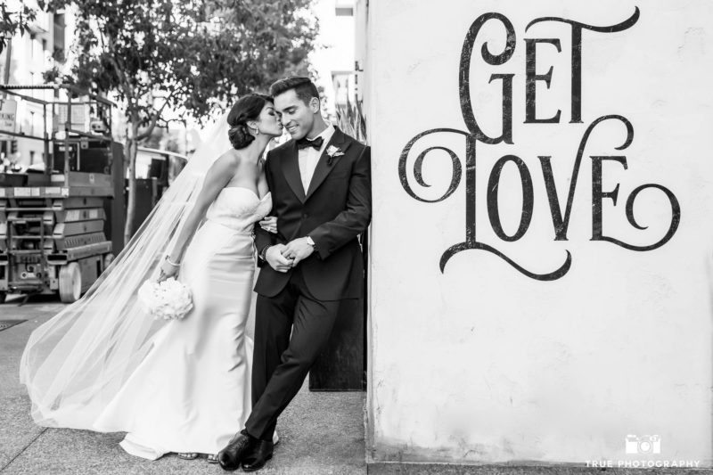 Bride kissing groom outside wall at Luce Loft in Downtown San Diego