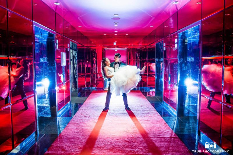 Bride and groom have fun in the hallway of their hotel