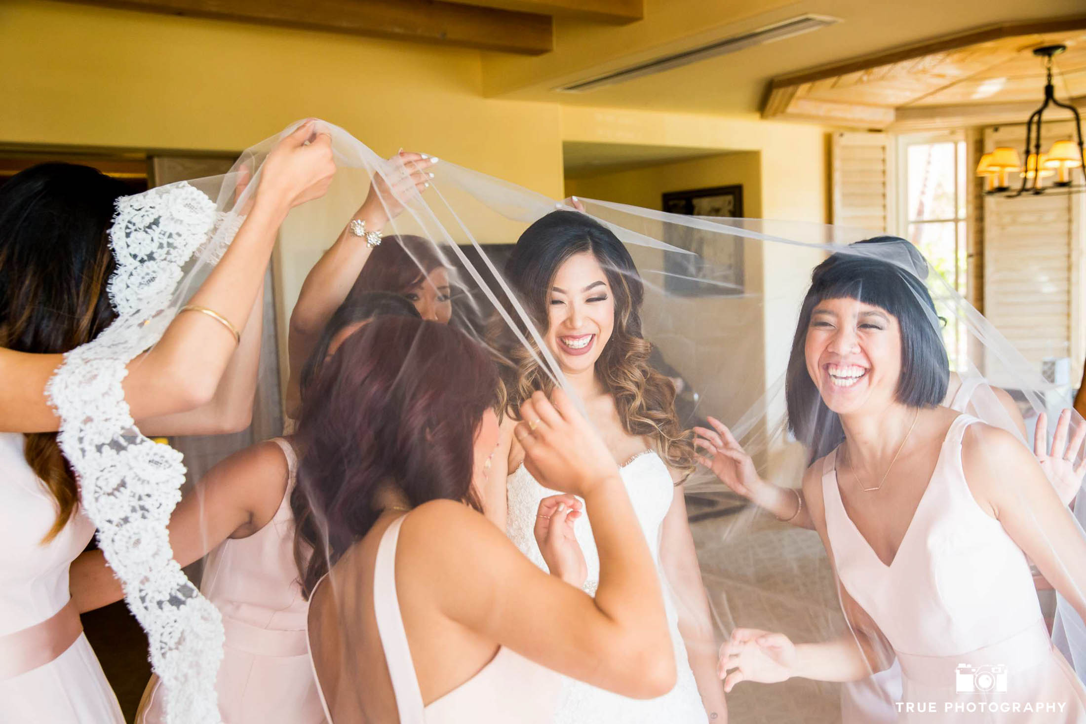 Bride and bridesmaids have fun while getting ready.