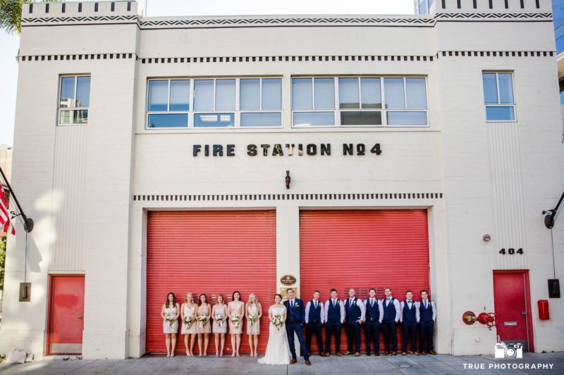 Wedding couple with their bridal party stand outside red doors at fire station in downtown