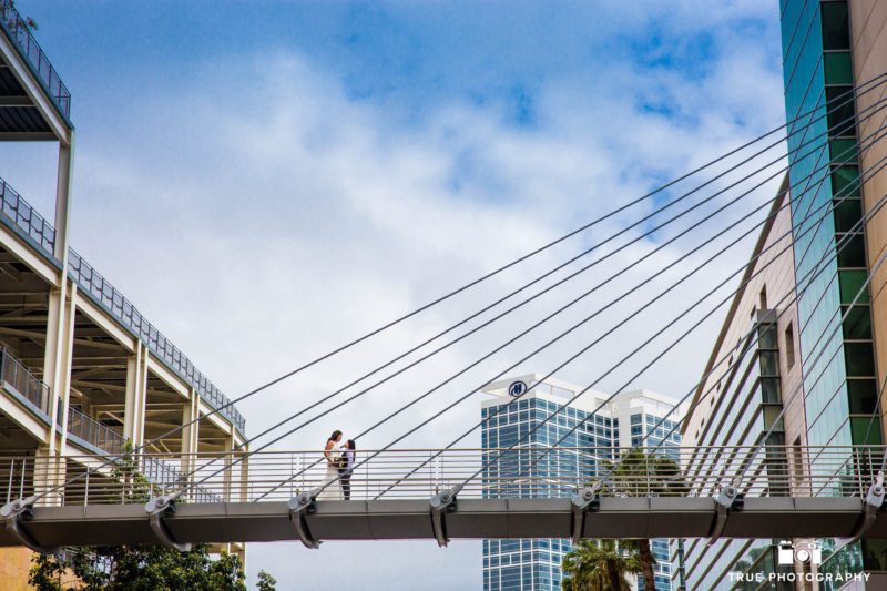 Wide angle photo of two brides embracing on bridge in downtown