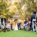 Bride and groom hold hands during outdoor wedding ceremony