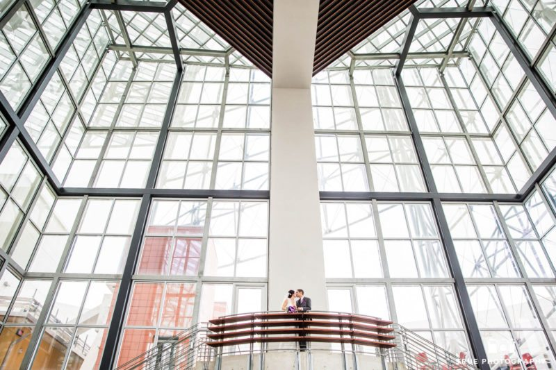 Environmental portrait of bride and groom kissing on stairs at modern library in downtown