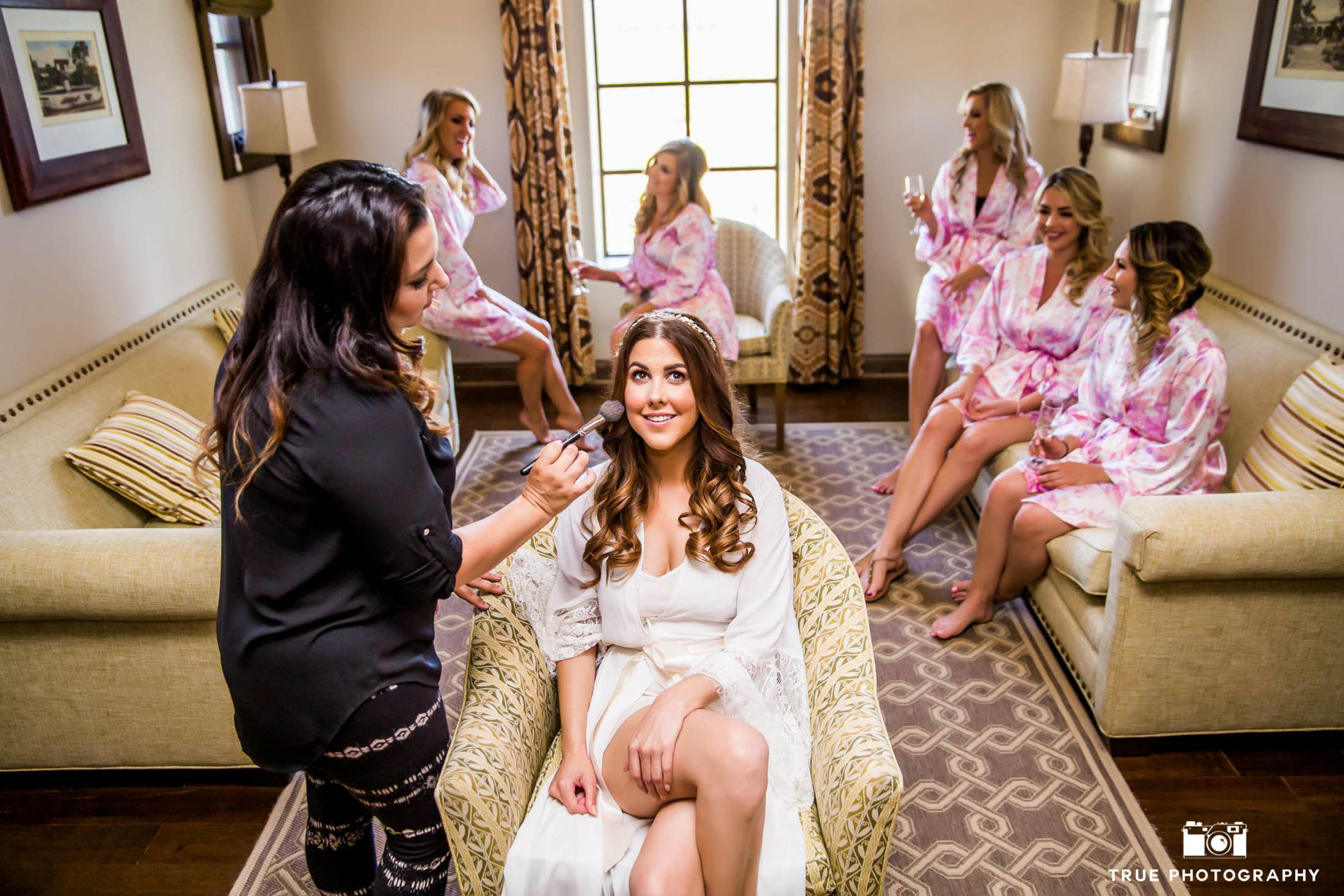 Bridesmaids chat while bride gets her makeup done.