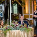 Bride and groom react with laughter during wedding toast speeches during reception
