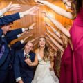 Bride and groom hold hands running under bridal party tunnel