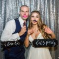 Bohemian bride and groom pose in Take-a-Pic photobooth during wedding reception