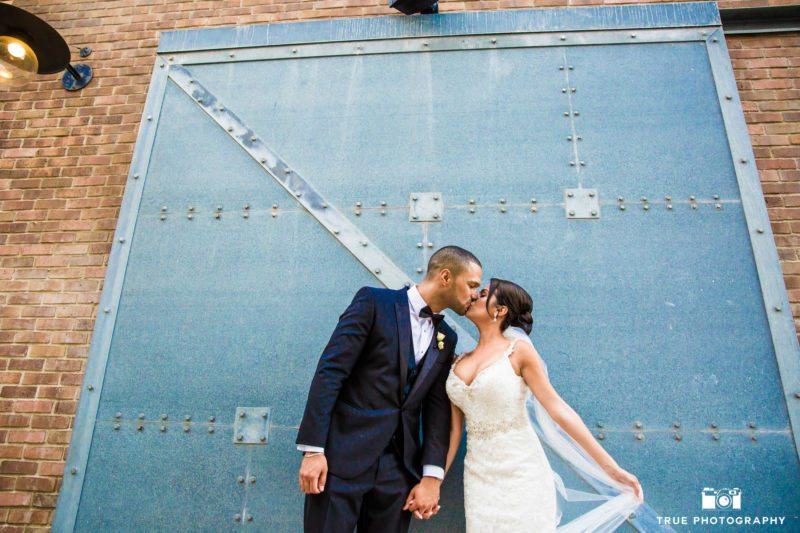 Stylized portrait of bride and groom kissing by blue door in downtown