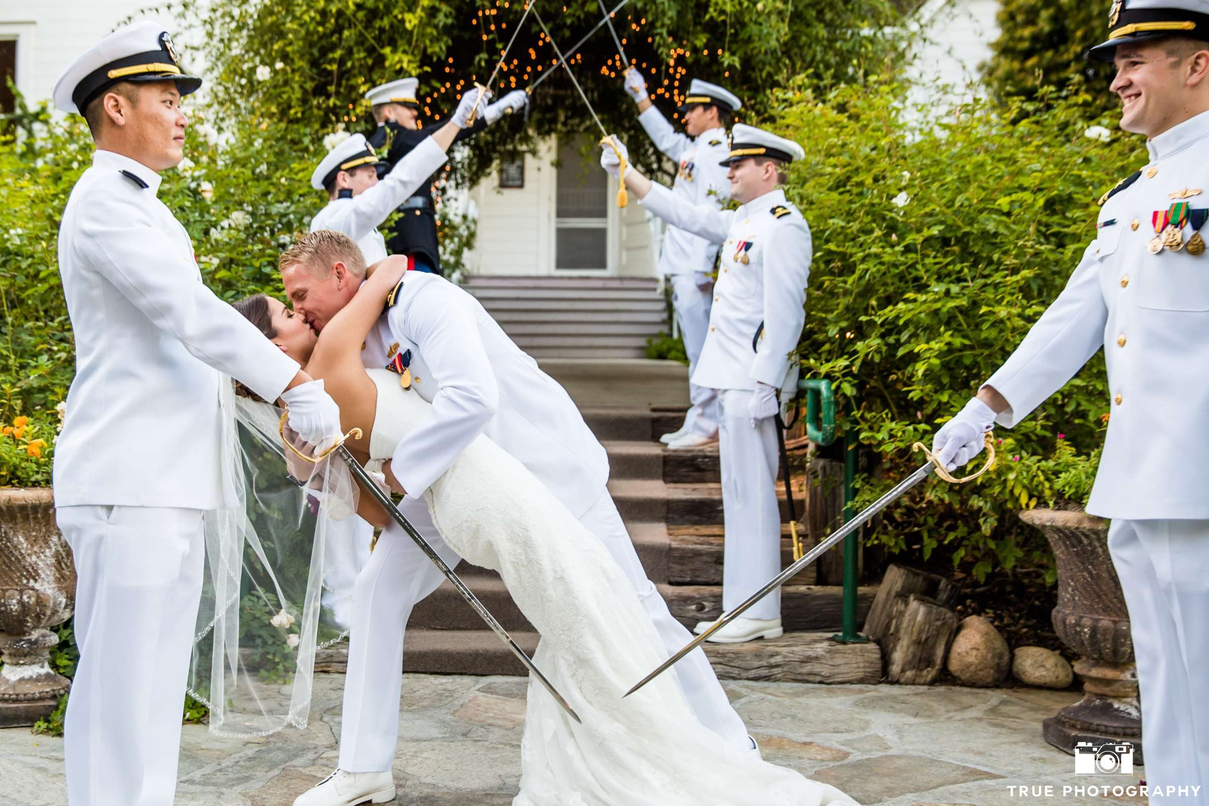 Newlyweds kiss beneath arch of swords.