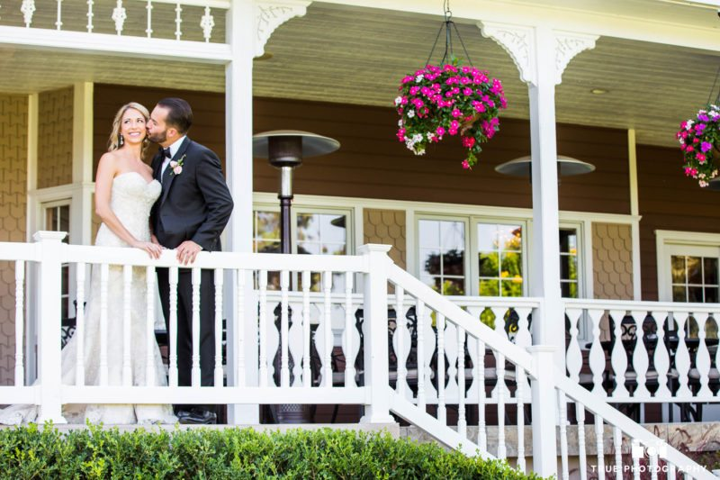 Groom kisses Bride on cheek while standing on stairs at Beverly Mansion