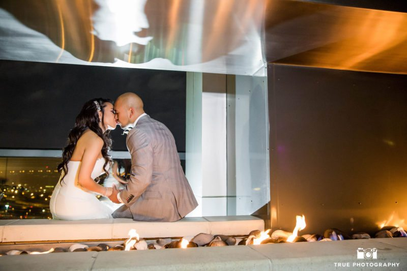 Bride and Groom kiss under fireplace at the Ultimate Skybox