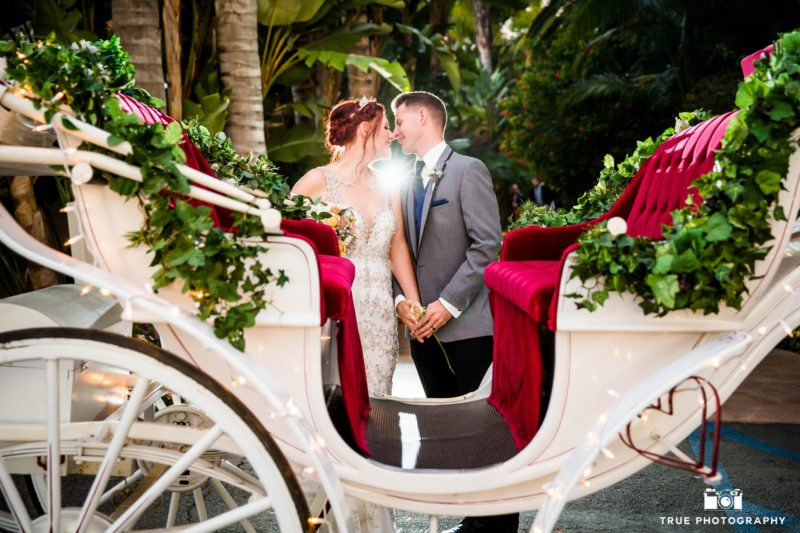 Bride and groom kiss by the carriage