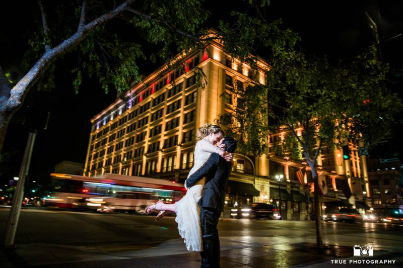 Night portrait of bride and groom kissing outside us grant hotel
