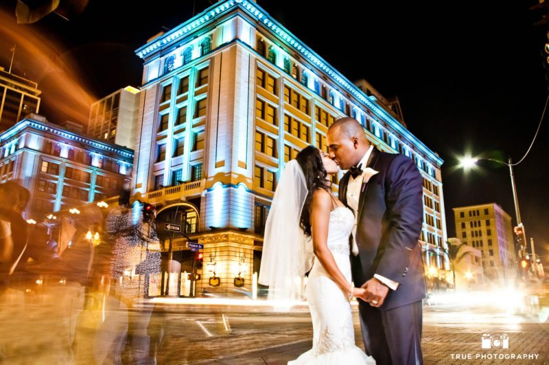 Creative night portrait of bride and groom outside US Grant in Downtown