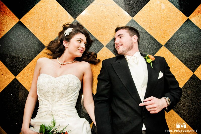 Bride and Groom lie on checkered tile and smile at one another