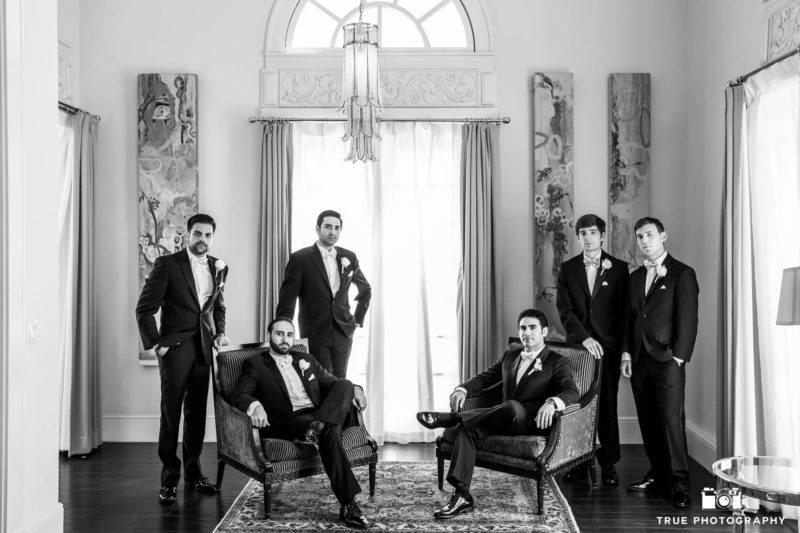 Groom and groomsmen sit in modern furniture at US Grant