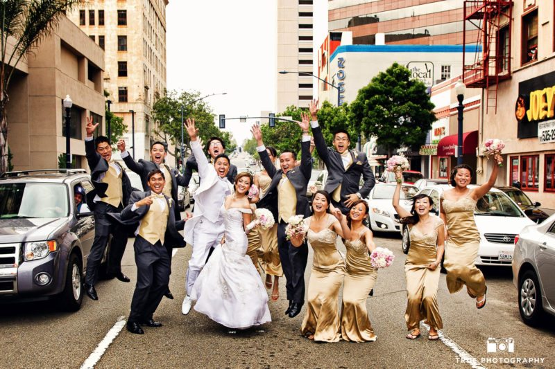 Wedding couple and bridal party jump in middle of Downtown street