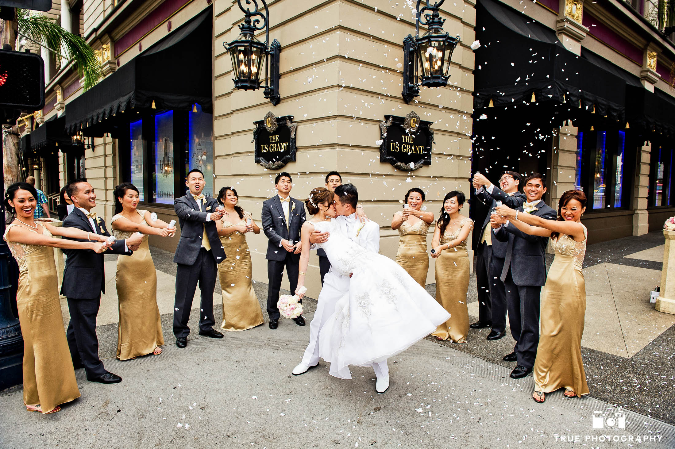 Bridal party throwing confetti while bride and groom kiss