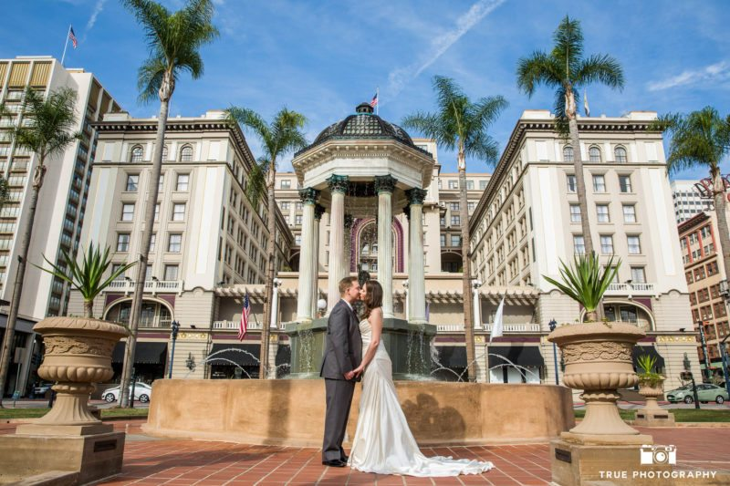 Bride and groom hold hands and kiss in front of water fountain outside the US Grant Hotel
