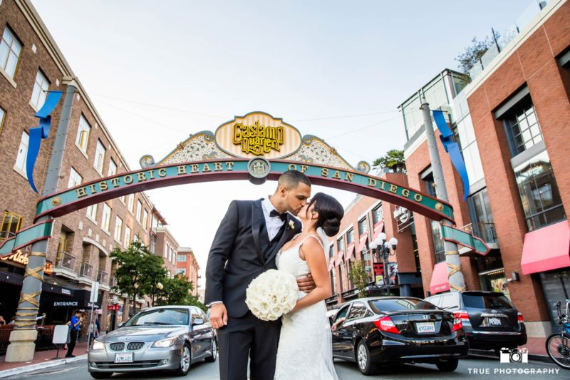 Bride and Groom kiss under gaslamp sign