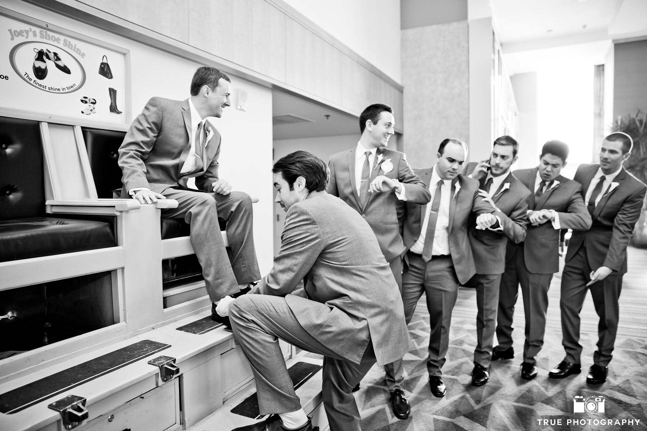 Groomsmen shining grooms shoes before wedding