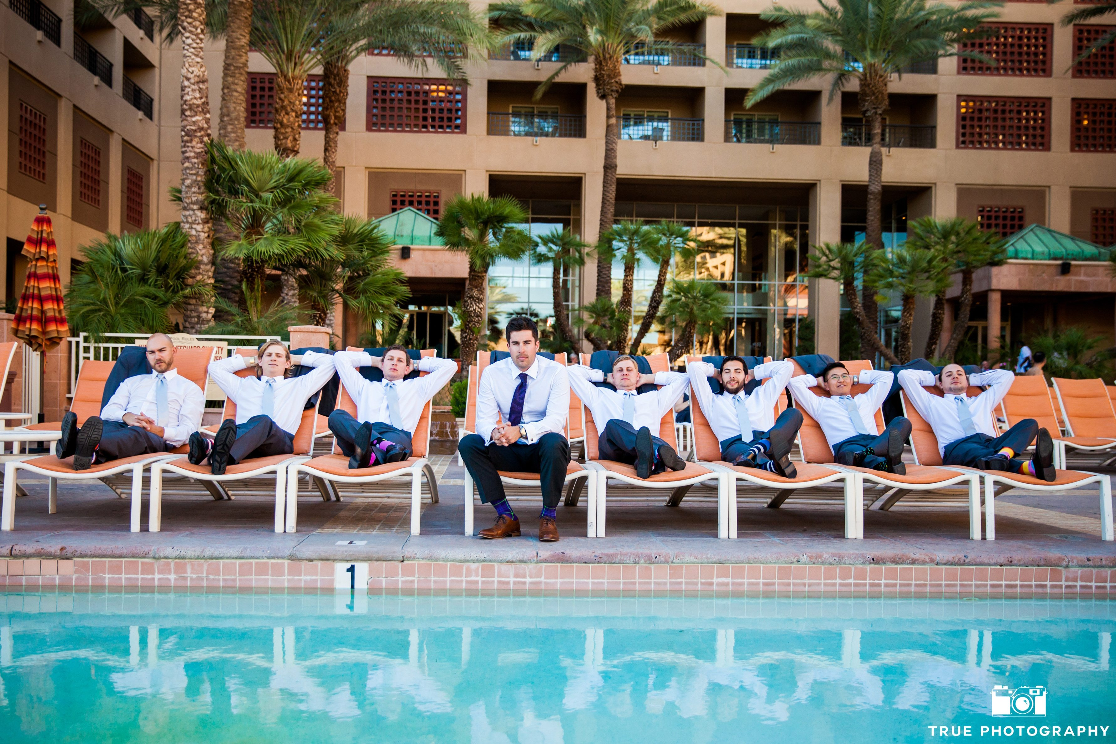 Groomsmen relaxing on lounge chairs before wedding