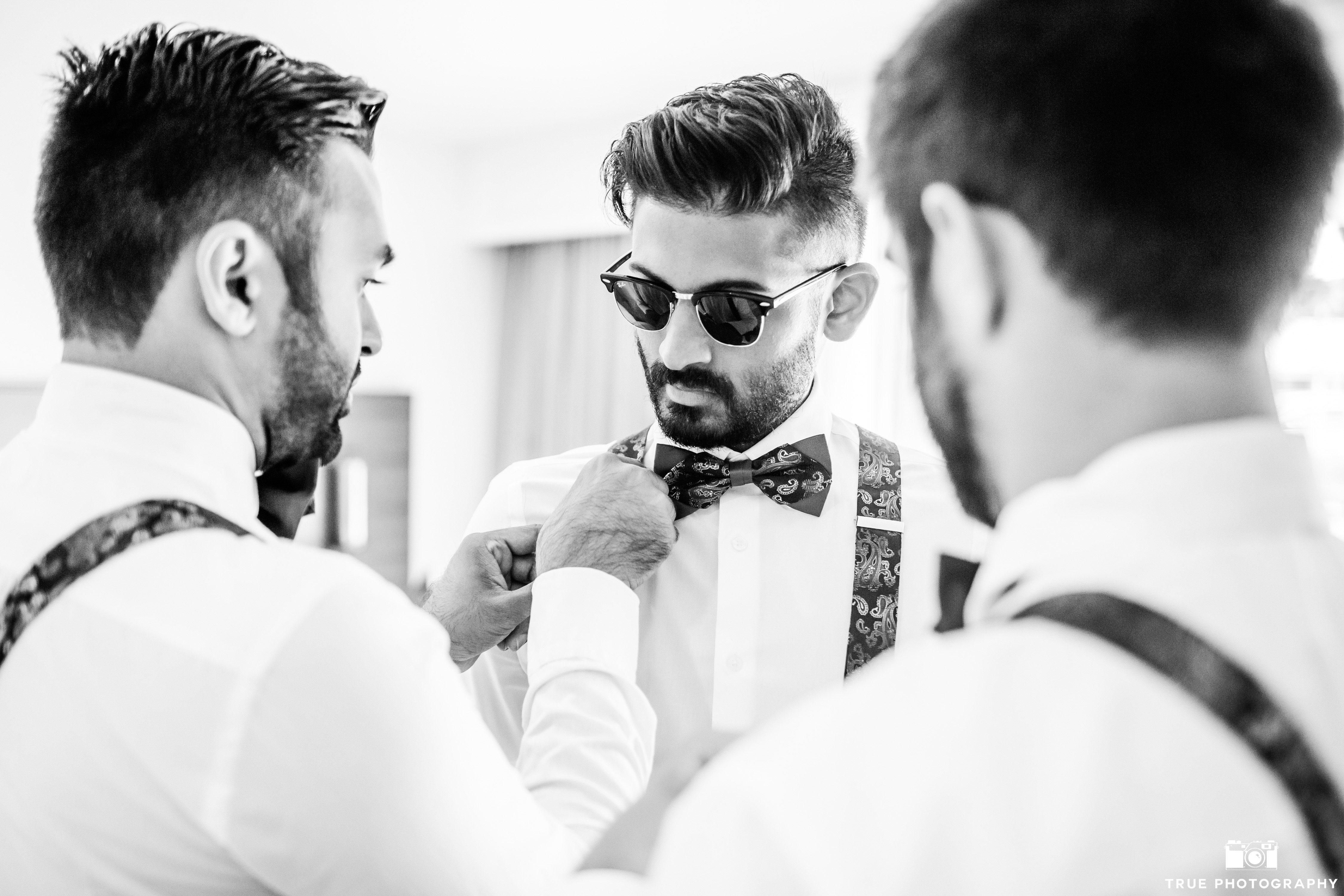 groomsmen getting ready bowtie and susperders wedding attire